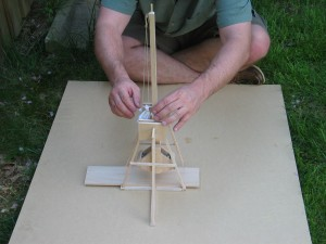Trebuchet in resting (vertical) position.  The counterweight is directly below the throwing arm at its lowest energy.